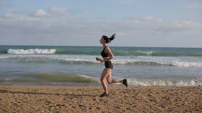 Mujer que corre solamente en la puesta del sol hermosa en la playa almacen de metraje de vídeo