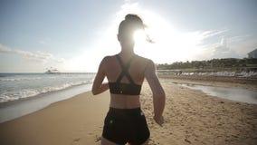 Mujer que corre solamente en la puesta del sol hermosa en la playa almacen de video