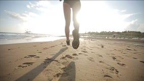 Mujer que corre solamente en la puesta del sol hermosa en la playa Cámara lenta almacen de metraje de vídeo