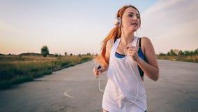 Mujer que corre y que escucha la música en los auriculares Imagenes de archivo