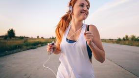 Mujer que corre y que escucha la música en los auriculares Fotografía de archivo