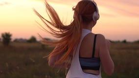 Mujer que corre y que escucha la música en los auriculares, cámara lenta metrajes