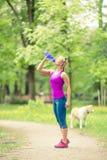 Mujer que corre y que activa con el perro en parque y madera verdes del verano Fotos de archivo