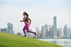 Mujer que corre y que se resuelve en la mañana en la ciudad imagen de archivo libre de regalías