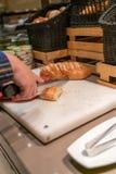 Mujer que corta el pan en el restaurante del buffet foto de archivo