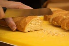 Mujer que corta el pan francés Imágenes de archivo libres de regalías