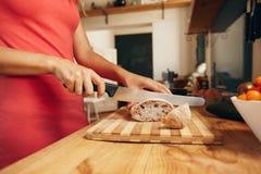 Mujer que corta la barra de pan en cocina fotos de archivo libres de regalías