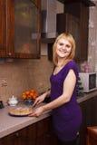 Mujer que corta la empanada de manzana caliente en la cocina Imagen de archivo