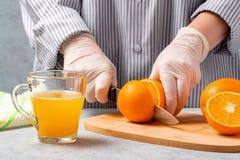 Mujer que corta las naranjas para hacer el jugo fresco imagen de archivo