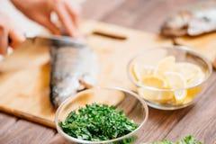 Mujer que corta los pescados crudos para el plato en la cocina imágenes de archivo libres de regalías