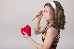 Mujer que corta un juguete del corazón con un cuchillo Fotografía de archivo