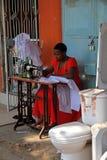 Mujer que cose en la calle al lado de un tocador Imágenes de archivo libres de regalías