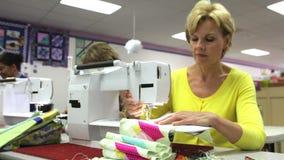 Mujer que cose usando la máquina eléctrica almacen de metraje de vídeo