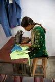 Mujer que cose varios pedazos de ropa en Agra para Pushpanjali Imagenes de archivo
