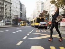 Mujer que cruza la calle Foto de archivo libre de regalías