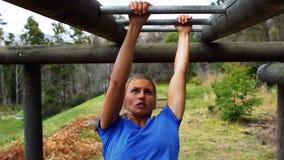 Mujer que cruza las barras de mono durante carrera de obstáculos almacen de metraje de vídeo