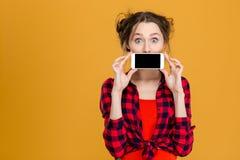 Mujer que cubre su boca con la pantalla en blanco del smartphone Foto de archivo