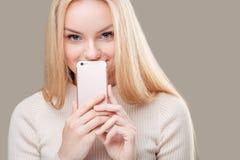 Mujer que cubre su boca con la pantalla en blanco del smartphone sobre fondo gris Foto de archivo libre de regalías