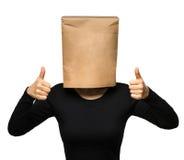 Mujer que cubre su cabeza usando una bolsa de papel Fotos de archivo