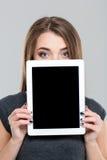 Mujer que cubre su cara con la pantalla de tableta en blanco Fotos de archivo