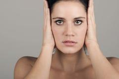 Mujer que cubre sus oídos Fotografía de archivo