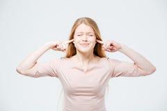 Mujer que cubre sus oídos con los fingeres Fotografía de archivo libre de regalías