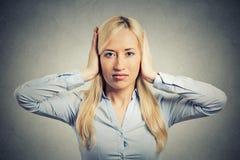 Mujer que cubre sus oídos que evitan la situación grosera desagradable Foto de archivo libre de regalías