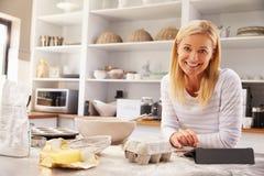 Mujer que cuece en casa receta de siguiente en una tableta Imagen de archivo libre de regalías