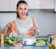 Mujer que cuece salmones y verduras al vapor Fotografía de archivo libre de regalías