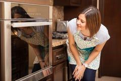 Mujer que cuece una torta y esperar Fotografía de archivo libre de regalías