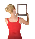 Mujer que cuelga el marco en blanco del arte Fotografía de archivo libre de regalías