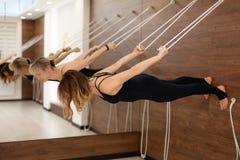 Mujer que cuelga en paralelo de la cuerda para tender la ropa a la cara de tierra abajo de la yoga practicante en marcas de estir imagen de archivo