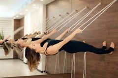 Mujer que cuelga en paralelo de la cuerda para tender la ropa a la yoga practicante de tierra en marcas de estiramiento en el gim fotos de archivo