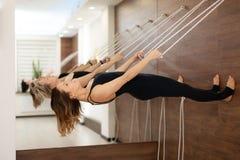 Mujer que cuelga en paralelo de la cuerda para tender la ropa a la yoga practicante de tierra en marcas de estiramiento en el gim foto de archivo libre de regalías