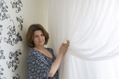 Mujer que cuelga para arriba sus cortinas blancas en la ventana Imagenes de archivo