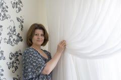 Mujer que cuelga para arriba sus cortinas blancas en la ventana Foto de archivo