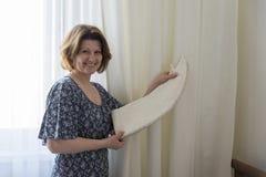 Mujer que cuelga para arriba sus cortinas blancas en la ventana Fotos de archivo