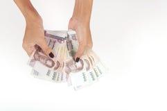 Mujer que cuenta Tailandia 1000 billetes de banco del baht Foto de archivo