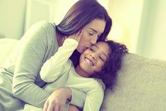 Mujer que cuida hermosa que besa a su hija en la mejilla fotos de archivo