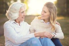 Mujer que cuida que tiene conversación con la madre mayor en el parque Imagenes de archivo