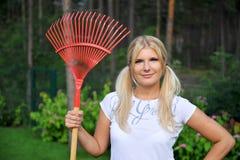 Mujer que cultiva un huerto bonita joven con los rastrillos Fotografía de archivo