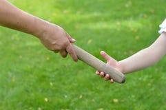 Mujer que da el bastón de la retransmisión en una mano del ` s del niño imagen de archivo