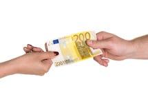 Mujer que da el billete de banco del euro 200 a un hombre Imagenes de archivo