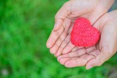 Mujer que da el corazón rojo en fondo de la hierba verde Fotos de archivo libres de regalías