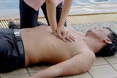 Mujer que da el CPR a ahogar al hombre, salvación de vidas del CPR Foto de archivo libre de regalías