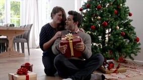 Mujer que da el regalo de Navidad de la sorpresa al marido metrajes