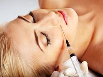 Mujer que da inyecciones del botox. Fotografía de archivo