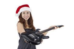 Mujer que da la guitarra eléctrica como regalo de la Navidad Foto de archivo