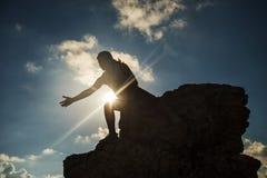 Mujer que da la mano de la ayuda en el pico de la colina Imagen de archivo