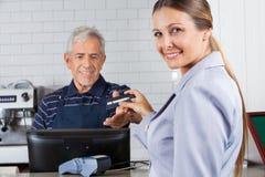 Mujer que da la tarjeta de crédito al cajero At Counter Foto de archivo